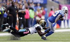 Indianapolis Colts' Frank Gore (23) runs out of the tackle of Jacksonville Jaguars' Johnathan Cyprien (37) during the first half of an NFL football game Sunday, Oct. 4, 2015, in Indianapolis. (AP Photo/Michael Conroy)