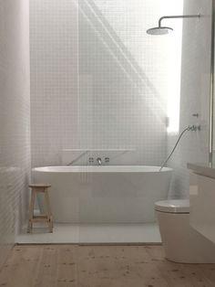 Interesante propuesta: bañera en la ducha con luz cenital. Todo en blanco y madera natural.