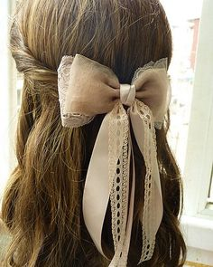 tie two ribbons together and fasten onto a bobby pin. no retying bows with each hairstyle