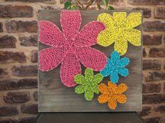 Fleurs hippies, réalisées avec la technique du string art ou encore du fil tendu. Elles sont sur un support en bois teinté aspect vieillit de taille 30/30 des pointes en acier poli et du fil pour crochet rose, jaune, orange, turquoise et vert.