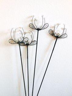 Svatební - zápich Zápichy jsou zhotoveny z černého žíhaného drátu a dozdobeny skleněnými korálky a třpytivým kroužkem z plastu. Délka zápichu je cca 48 cm, velikost květenství má průměr 7 cm. Zápich se hodí do květináčů, suchých vazeb a různých dekorací. Cena za kus. Drát je ošetřenproti korozi, ve velmi vlhkém prostředí může chytit patinu.