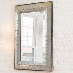 """Metal Industrial Rivet MirrorThis distressed galvanized tin mirror will work well in an outdoor or indoor location. The aged brass rivet detailing and dark metal trim around the frame add industrial appeal. Hangs vertically. Mirror dimensions: (27""""Hx17.5""""W). (37""""Hx27.5""""Wx1.5""""D)."""
