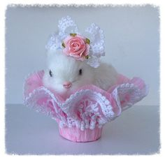A sweet furry bunny is wearing lace and a flower in her hair. She is sitting in a basket made from crepe paper and lace. So beautiful for Easter or