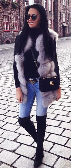 trendy outfit idea : black sweater fur vest bag skinnies over knee boots
