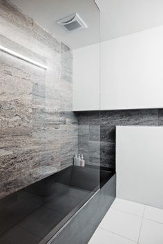 The residence's two bathrooms present distinct material identities: In the main bathroom, located on the lower level near the couple's bedroom, a custom stainless-steel bathtub designed by Gil contrasts with a wall clad in silver travertine.