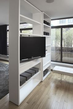 Magdalena Keck Interior Design - Tribeca Apartment, room divider shelf with rotating TV.