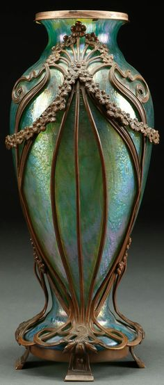 A BOHEMIAN IRIDIZED GLASS AND BRONZE MOUNTED VASE, LATE 19TH CENTURY. Comprising a Rindskopf green iridized glass vase contained in a tooled bronze art nouveau frame of stylized florals. Height 14 inches (36 cm).
