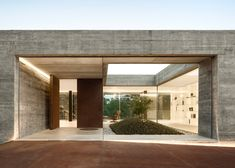 A glazed wall framed by thick concrete fronts this house built into a grassy hillside in Penafiel, Portugal.