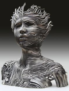 Texas-based sculptor Gil Bruvel manipulates ribbons of cast stainless steel to create spectacular figurative sculptures for his Flow series.  Bruvel's collection often features a sense of duality. In his piece titled Dichotomy, the artist presents the bust of his figure constructed in two patterns. One half of the sculpture consists of vertical lines, while the other half is composed of horizontal ribbons.
