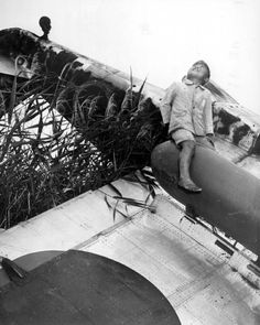 "Japanese boy atop the external drop tank slung under the wing of a crashed, wrecked Kawasaki Ki-61 Hien ""Tony"" at an airfield on Honshu, Japan in the immediate aftermath of the Pacific War. 1945."