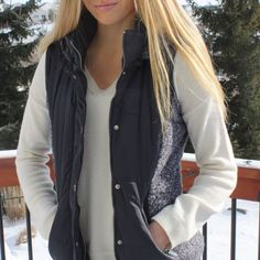 Vests are the perfect addition to your closet for fall! Worn over a teeshirt or button down, we love the mixed texture of this vest. Boucle sides and trimmed, detachable hood make it ultra flattering. Both a silver toned zipper and snap closure along with zippered pockets add to the fine details of this piece. This puffer vest is a must have!
