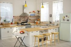 Of course, the minimalist look of a modern white kitchen is not right for everyone. In this final space we see the glory of a fully equipped cooking space with every design element carefully chosen. From a vintage-inspired refrigerator to a folding bistro table and butcher block countertop, this kitchen is warm, cozy, and just a little bit quirky.