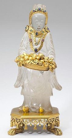 <b>Rock Crystal Gem Set Figure, Retailed by Cartier</b><br />rock crystal carving of a standing Guanyin bearing a fruit-filled basket and with gold adornment set with ruby, sapphire, and emerald cabochons, supported on a swag and tassel decorated plinth raised on cast and applied paw feet. Accompanied by likely original presentation silk-lined Cartier retailer's box.<br />10 in.<br /><br /><br /><br />Estate of a Lady, Washington, D.C.<br />With break having an early repair; minor chip to…