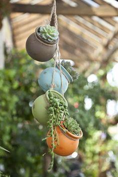 Estes vasinhos em formato de bola foram presos por corda de fibra natural e pendurados de forma organizadamente displicente. Um charme....