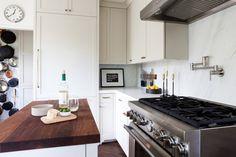 pale oak cabinets, white dove walls, warm butcher block island, retro clock