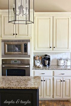 cream colored cabinets, white subway tile backsplash, island painted a contrasting color