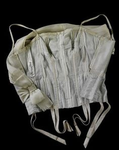 Inside of Vintage Doir bodice- This image shows the interior of a bodice, part of an outfit designed by Christian Dior (1905-57). The full ensemble consists of a skirt and bodice of lightweight organza, which float on a complex under-structure of net and boning in the bodice, and tulle in the skirt.   In-built corsetry was typical of couture garments, particularly for evening wear, so the client could simply step into her garment. In this case, even suspenders for stockings are included.
