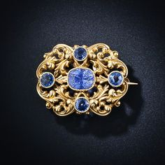 Art Nouveau Sapphire Brooch - center Ceylon cushion cut sapphire 2.4 carats, 4 round cut Montana sapphires 1.0 tcw, 14 kt gold, circa 1900. Love the scroll work