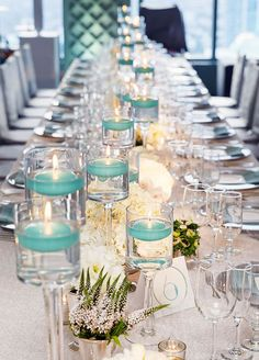 Long banquet tables covered in a seemingly endless array of white flowers interspersed with floating turquoise votive candles in varying heights. #WeddingCenterpieces