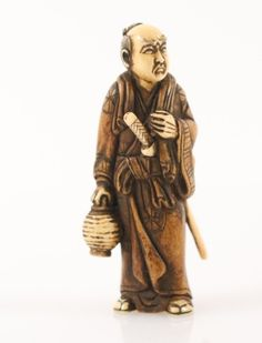 "Japanese, Late 19th/Early 20th century. Carved and tea stained ivory figural netsuke depicting a man, likely a warrior standing at full length wearing long robe and with sword at side, holding a rounded lantern. Marked in inlaid mother of pearl circular accent on lower side with marks. Approximate height 2.75""."