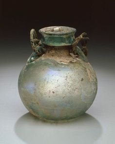 Roman Aryballos made to be suspended: Green iridescent Glass, Oil flask, free-blown with attached glass and bronze handles; wheel-cut lines around center of body. Antique Glass Bottles, Antique Glassware, Historical Artifacts, Ancient Artifacts, History Of Glass, Glas Art, Roman History, Roman Art, Bottles And Jars
