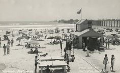 The beach during World War II: lifeguard station and Dwight's Beach Stand in Huntington Beach, California, with a Navy vessel at the end of the pier.
