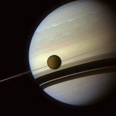 Spacecraft Cassini orbiting Saturn has recorded yet another amazing view. Titan, Saturn's largest moon, appears above. The rings of Saturn are seen as a thin line because they are so flat and imaged nearly edge on. Details of Saturn's rings are therefore best visible in the dark ring shadows seen across the giant planet's cloud tops. Image Credit: NASA/JPL-Caltech/Space Science Institute/J. Major.