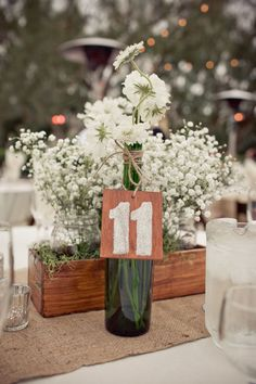 table number on wine bottle, wooden box with flowers in mason jars