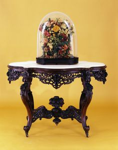 In 1866, Mary Todd Lincoln purchased a Rococo Revival style parlor set for  her Chicago, Illinois home. This exuberantly carved table, part of the set,  cont...