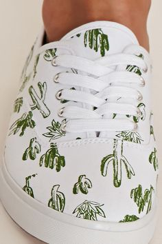 Style Deals - A pair of canvas plimsolls with a lace-up top and an allover cactus print.