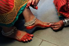 A Panaghat dancer gets her feet painted with organic colour.