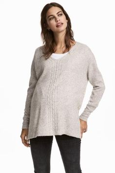 Slightly wider jumper in a soft knit containing some wool with a V-neck and cable-knit details. Dropped shoulders, long sleeves and pearly buttons at the si