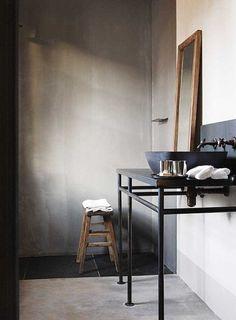 Marmer stuc op de wand en op de vloer. Stoer wastafelmeubel. Kranen en de waskom maken het beeld af.