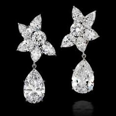 An important pair of diamond ear clips, by Harry Winston Each set with a detachable pear-shaped brilliant-cut diamond, weighing 6.94 and 7.00 carats, to a cluster surmount of pear, marquise and round brilliant-cut diamonds, mounted in platinum,