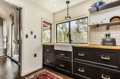 Petite kitchen remodel; vintage stove, open shelving, apron sink, vintage pendant light, unlacquered brass hardware, Anatolian rug, black cabinets, butcher-block countertops, beveled subway tile with gray grout; Design by Brooke Davis, Instar Properties
