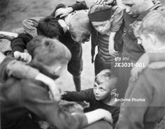 A group of boys stand in a circle, huddled arm-in-arm, as a young boy. Male Friendship, Young Boys, See Picture, Arms, Middle, Stock Photos, Group, Couple Photos, Pictures