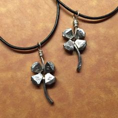 """A four-leaf-clover / Shamrock, crafted from the heads of steel horseshoe nails. Cut/sanded/soldered together...the stem is one of the """"head-less"""" portions of a horseshoe nail. Suspended from a sterling silver loop and and 18-20 inch black cord necklace. - $35.00"""