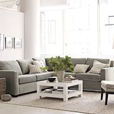 room with square sectional couch, coffee table and chair