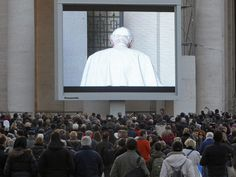 People watch a giant screen showing Pope Benedict XVI in St. Peter's Square, at the Vatican on Thursday.