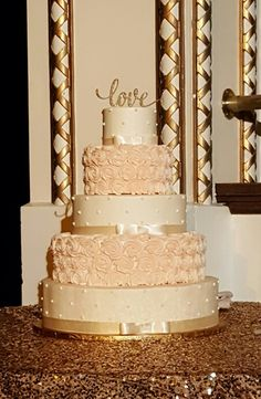 Ivory, blush and gold romance! This wedding cake covered with blush buttercream rosettes, ivory ribbons and a sweet gold topper.