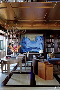 A gilded ceiling shines in the ebony-paneled library of a New York City apartment | archdigest.com