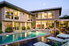 Originally a single-story modern home built in 1959, this contemporary home was remodeled to include a second-story addition. Stone, taupe synthetic wood siding and stucco were used for the home exterior, while a deck and luxurious pool area were added to create a stunning backyard area.