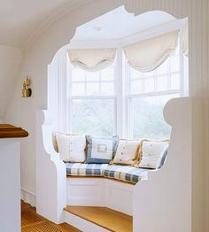 Plump cushions in soft, muted tones make this sunny window seat the perfect place to curl up with a good book. The carved valance curves snugly around the bay window, providing a sense of coziness and privacy. You could even store your books and magazines etc. underneath!