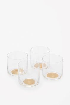These tumbler glasses are made from hand-blown crystal with a golden dot in the base for a subtle contrast. Each set contains four matching glasses.