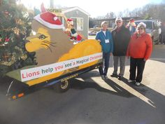 Lions Mary Tremblay, Chris Gies, and Dave Hartenstein are shown by the Lions float, preparing to march in the Hampton Christmas Parade. Courtesy photo