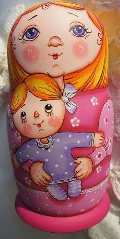 Blue-eyed matryoshka (Russian nesting doll) in its pink outfit is holding a doll. #Russian #folk #art #matryoshka