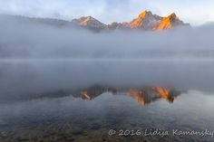 Alpenglow lights up Mount McGowan's summit above a foggy Stanley Lake at sunrise.