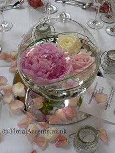 Elegant fishbowl design with floating flowers – peonies, roses and hydrangea florets - placed on a mirror plate scattered with rose petals.  Grass threaded with pearl beads completes the design and creates some added interest.