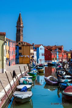Brightly-coloured houses are reflected in the water of the canals with the leaning campanile of Chiesa di San Martino in the background | Darby Sawchuk
