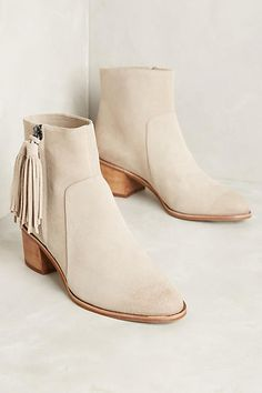 Suede booties with a classic silhouette and a touch of tassel, from…